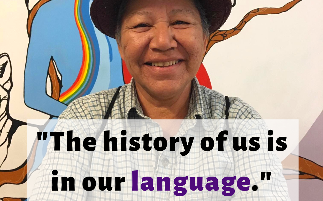"Rainbow Spirit Woman wearing a brown hat, smiling in front of a mural with her arms crossed. Text on the image reads ""'The history of us is in our language.' Rainbow Spirit Woman #NonBinaryDay"