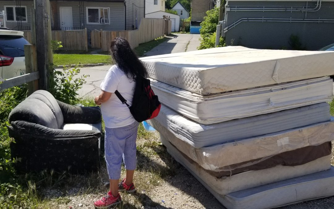 A woman in a white t-shirt with a backpack stands looking at a pile of mattresses and an old couch in an alley