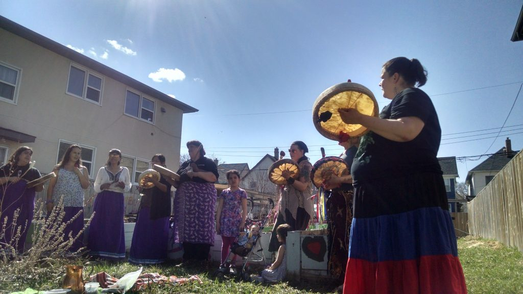 Group of women singing with hand drums in a community garden on a sunny day.