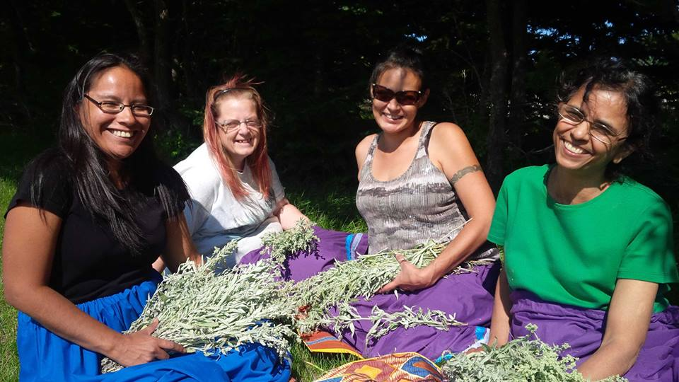 Four women smiling at the camera sitting on the ground holding sage they just picked.
