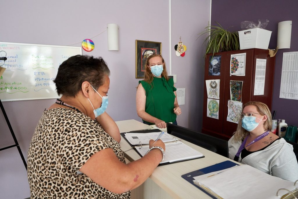 Three women wearing masks at a reception desk