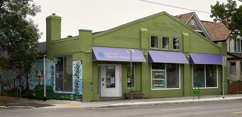 front of WCWRC building: Green building with purple awning and mural and trees on east side.